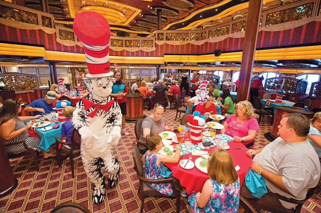 """The Cat in the Hat walks amid cruise diners during the """"The Green Eggs and Ham Breakfast with the Cat in the Hat and Friends"""" onboard the Carnival Freedom. The featured dining opportunity with characters out of Dr. Seuss' books is staged in the Carnival Freedom's Chic Dining Room and offers playful foods straight from Dr. Seuss's imagination – green eggs and ham, moose juice and goose juice, along with colorful fruit and pancake stacks, funky French toast and more. (Andy Newman/Carnival Cruise Lines)"""